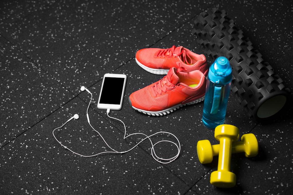 Bild på träningsutrustning för hemmet. Bland annat hantlar och en foam roller.